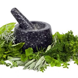 Black mortar and pestle with fresh picked herbs, over white background.